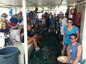 Pacific Whale Foundation guests and crew work together to remove a large net from the ocean during an Eco-Adventure