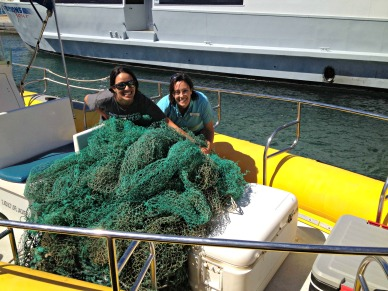 PWF Eco-Adventures staff pose with derelict fishing net that they pulled out of the ocean