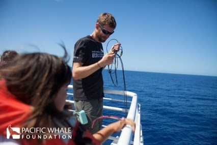 naturalist using the hydrophone so children can hear the whales